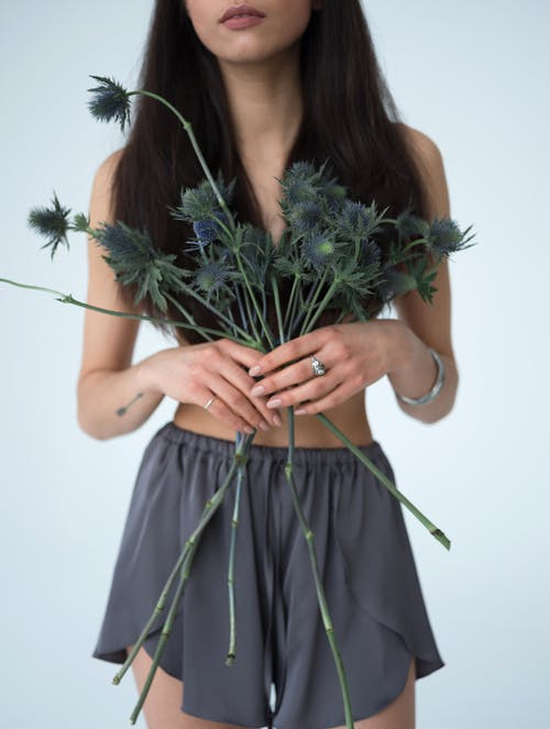 Crop fit woman with sea holly flowers