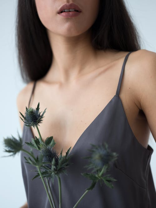 Crop pensive young woman in summer top holding bunch of beautiful violet Eryngium plant