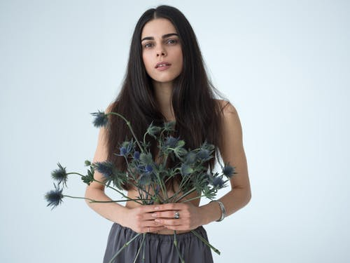 Beautiful tender young female with long dark hair covering breast holding bunch of sea holly flowers and looking at camera