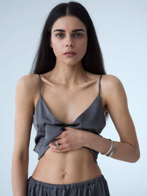 Confident young fit woman showing abdominal muscles