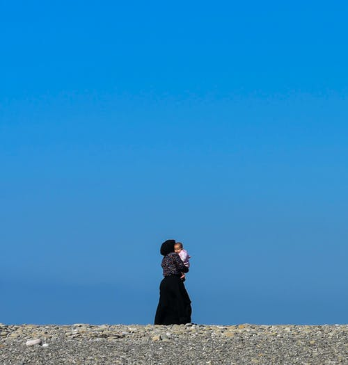 Woman in Black Dress Standing on Gray Sand