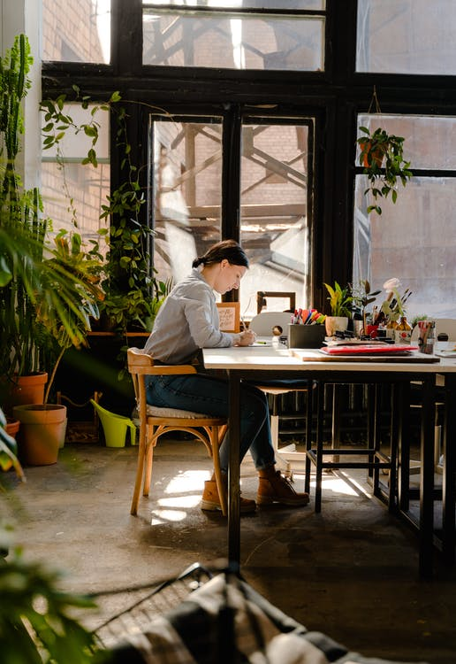 Photo of Woman Sitting by the Table While Writing