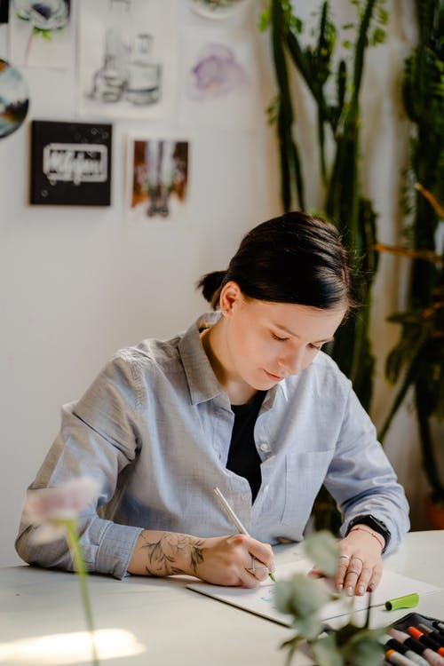 Photo of Woman Writing on White Paper