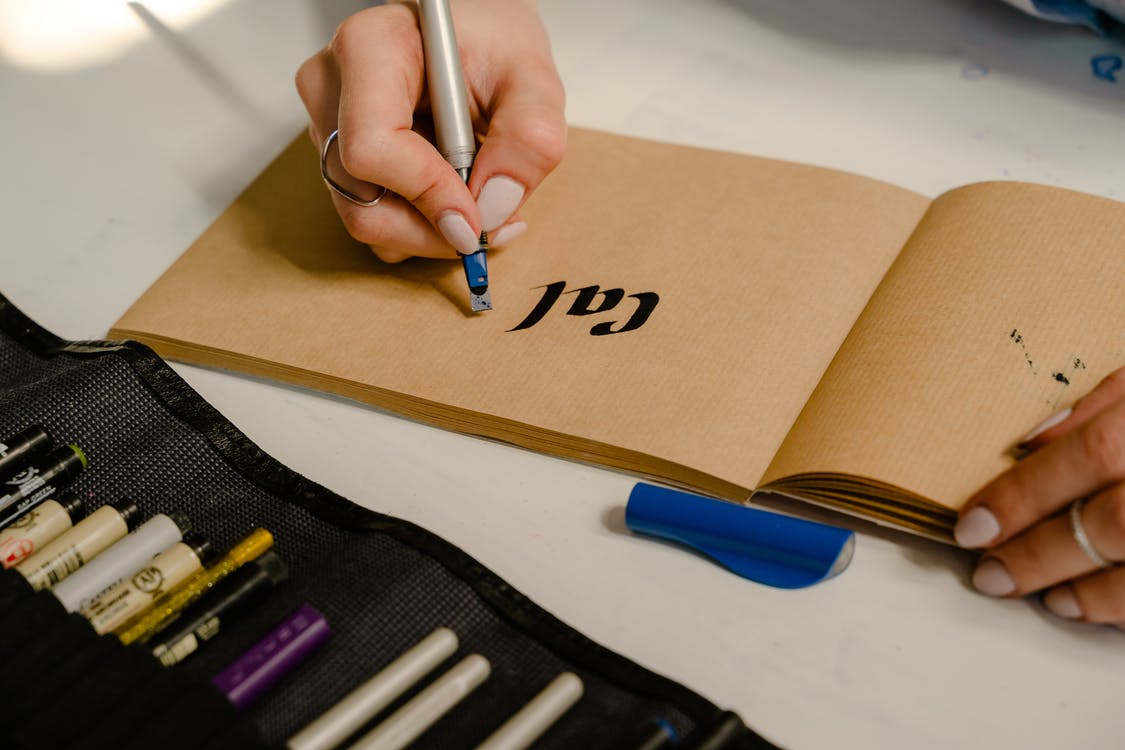 Photo of Person Writing on Brown Paper