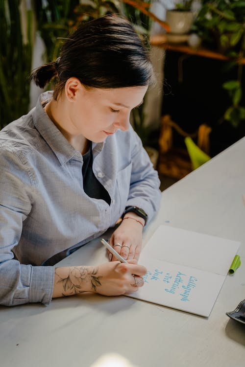 Woman in Gray Dress Shirt Writing on White Paper