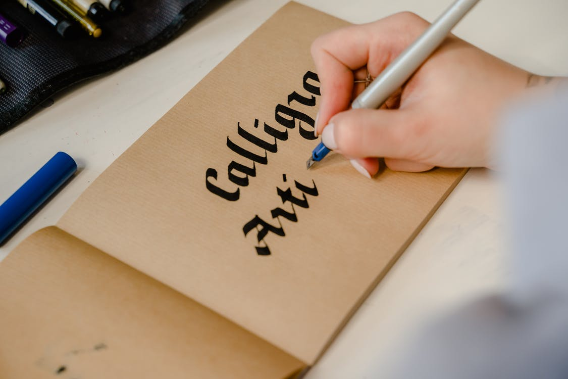 Person Writing on Brown Paper
