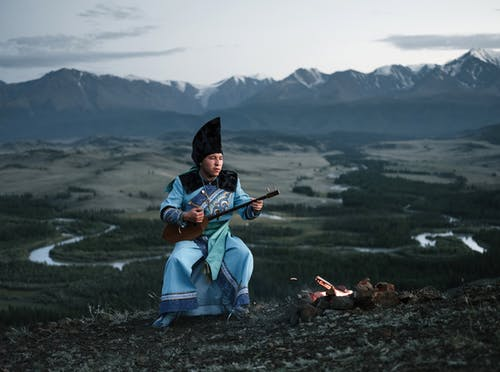 Full body of concentrated Mongolian male musician in national costume sitting near bonfire and playing traditional musical instrument against picturesque mountains