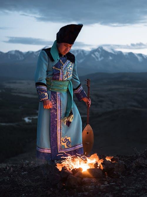 Young Mongolian male musician standing near bonfire with dombor