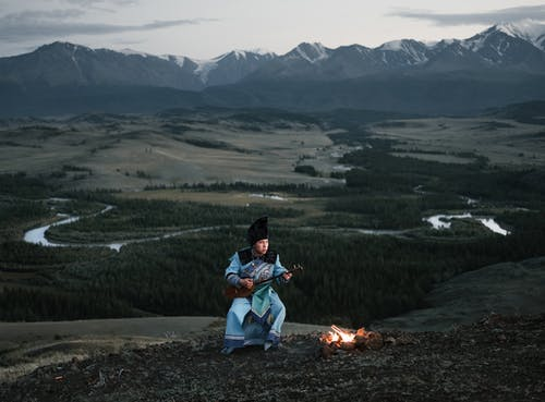 Young Mongolian male musician playing dombor in valley