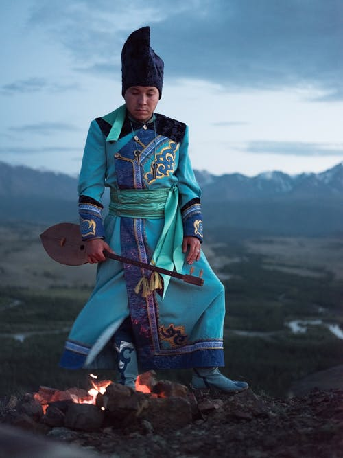 Thoughtful young Mongolian male in traditional clothes looking at bonfire while standing in valley with folk musical instrument