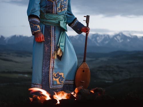 Crop person standing near bonfire with Mongolian folk instrument in valley