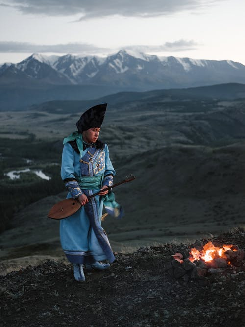 Full body of Mongolian guy in national costume with folk musical instrument standing near bonfire against beautiful mountainous valley
