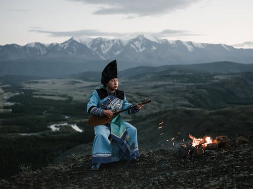 Tibetan young man playing lute sitting against mountains in twilight