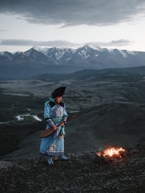 Tibetan young man holding lute while standing against rocky scenery at dusk