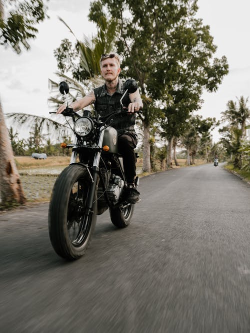 Man Riding Black Motorcycle on Road