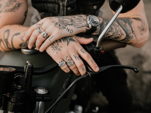 Photo of Person's Hands With Tattoos and Rings