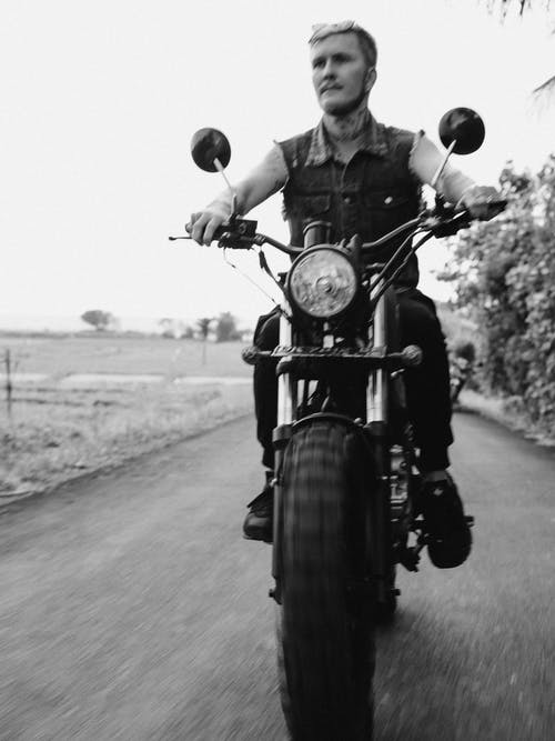Grayscale Photo of Man Riding Motorcycle