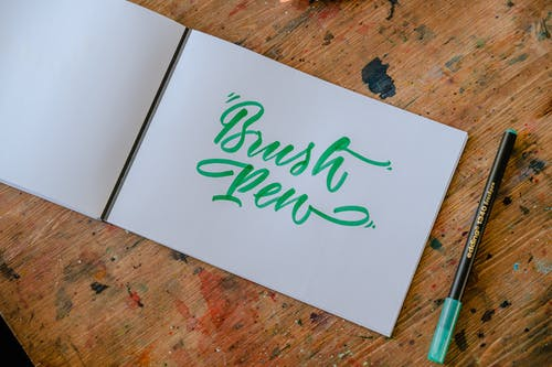 Top view of rectangular paper album with BRUSH PEN title written with green felt pen and original letter font on wooden desk with ink spots in workshop