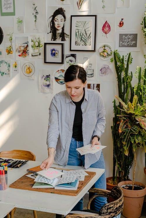 Young female designer choosing drafts at work in workshop