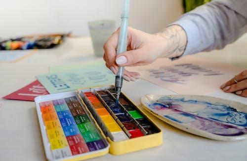 Crop unrecognizable artist using art brush and watercolor palette