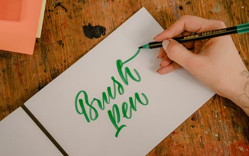 Top view of crop anonymous female designer writing BRUSH PEN title using felt pen and creative letter font while sitting at wooden table with ink spots on surface