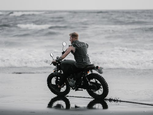 Biker riding motorcycle on ocean beach in stormy weather