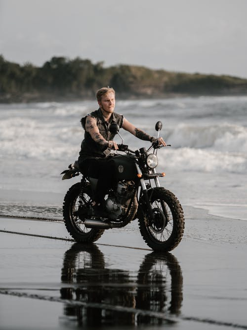Tattooed motorcyclist riding bike along ocean coast in evening
