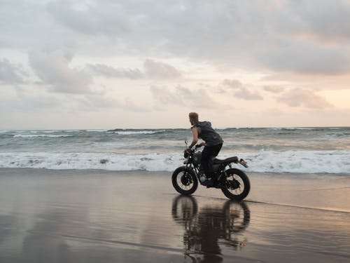 Side view of faceless male rider leaned forward while riding bike on wet sand near ocean with foamy waves under cloudy sky at sundown