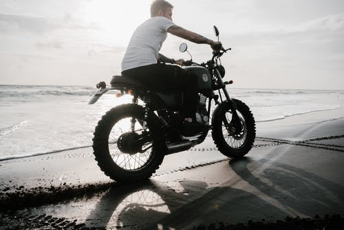 From below side view of unrecognizable tattooed guy in t shirt riding motorbike on sand beach leaving traces and creating splash effect near sea in evening in back lit
