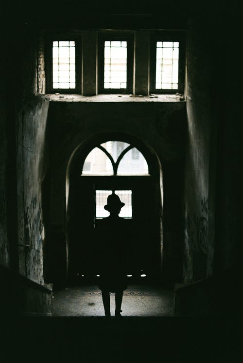 Anonymous silhouette of person in hat standing on stairs in front of arch door with fenced windows above in aged building with shabby walls