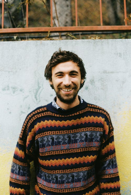 Happy adult bearded male with toothy smile in knitted sweater standing near colorful shabby wall with metal fence above in daylight and looking at camera