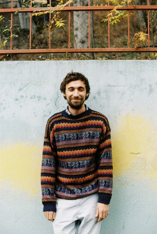 Slim smiling man standing near concrete wall in autumn