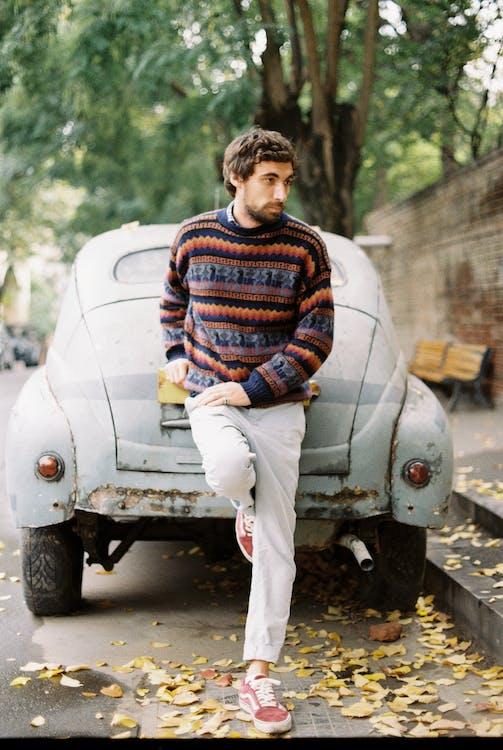 Male model standing leaned on old car near sidewalk