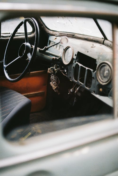 Interior of vintage automobile with steering wheel and speedometer with arrow on rusty surface near wire bundle in daylight