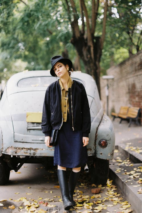 Trendy woman standing near retro auto in asphalt road