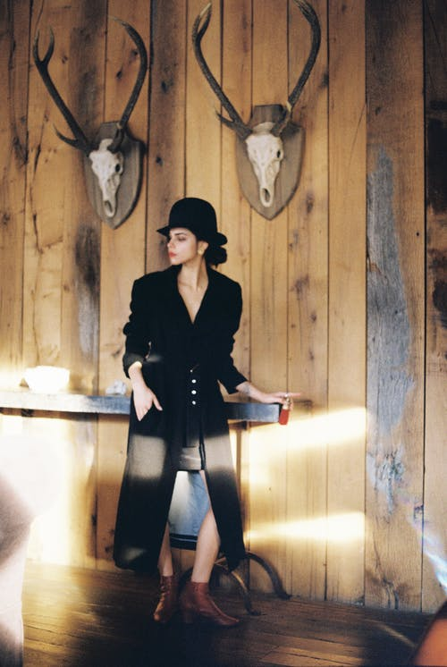 Stylish woman in trendy outfit standing near wooden wall
