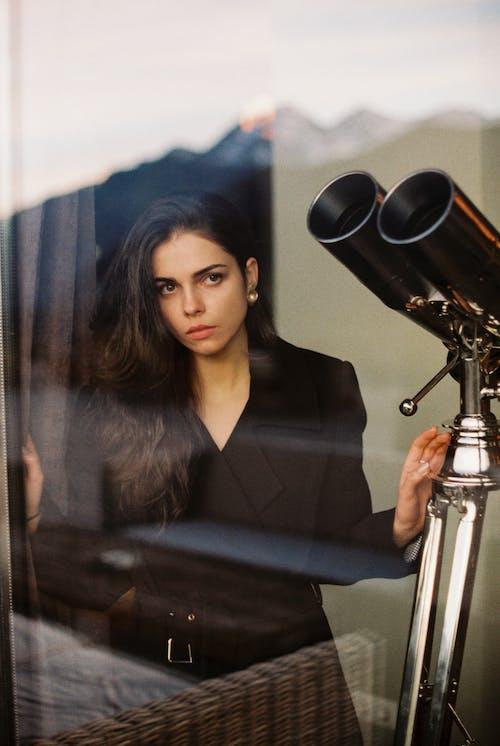 Young stylish woman standing near window