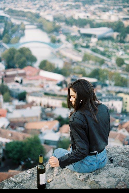 Serious woman sitting on stone parapet