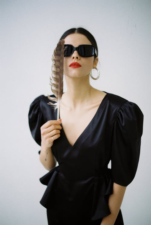 Emotionless young female in stylish black dress and sunglasses holding feather in hand and looking at camera