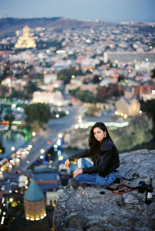 Unemotional woman sitting above city