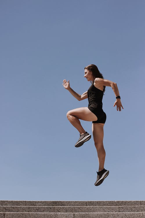 Woman in Black Tank Top and White Shorts Jumping