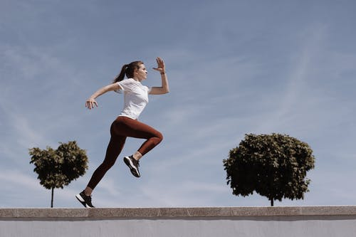 Woman in White Shirt and Orange Shorts Jumping on Gray Concrete Pavement