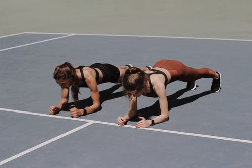 Woman in Black Sports Bra and Shorts Doing Push Up