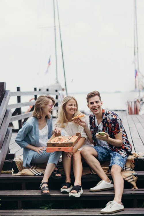 3 Women Sitting on Wooden Bench