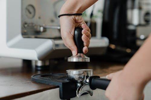 Unrecognizable female bartender pressuring ground coffee in portafilter with tamper for preparing tasty aromatic espresso during work in coffee house