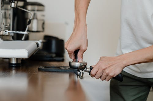 Crop professional barista preparing coffee at wooden counter