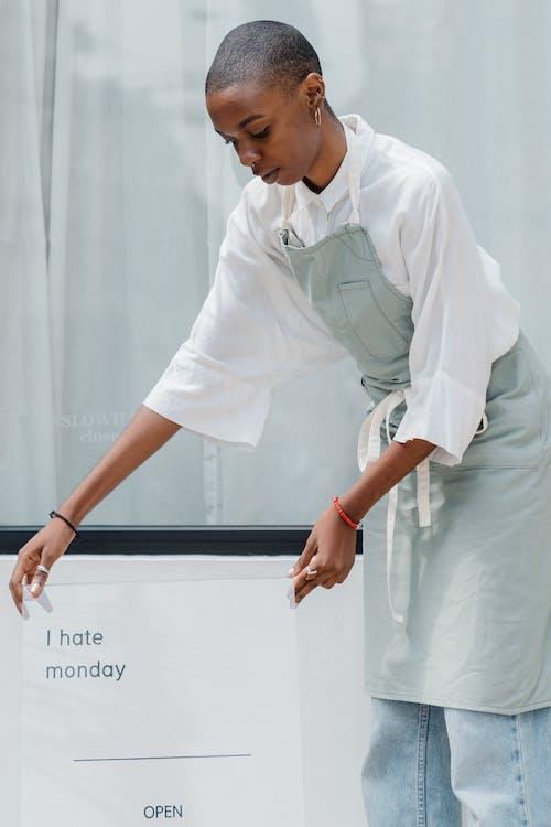 Content black female worker establishing signboard outside cafe