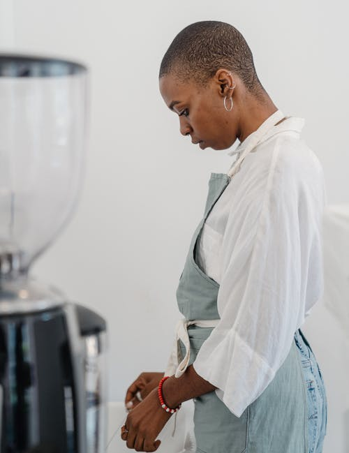 Side view of concentrated young African American female bartender with short hair wearing apron looking down while standing behind coffee grinder