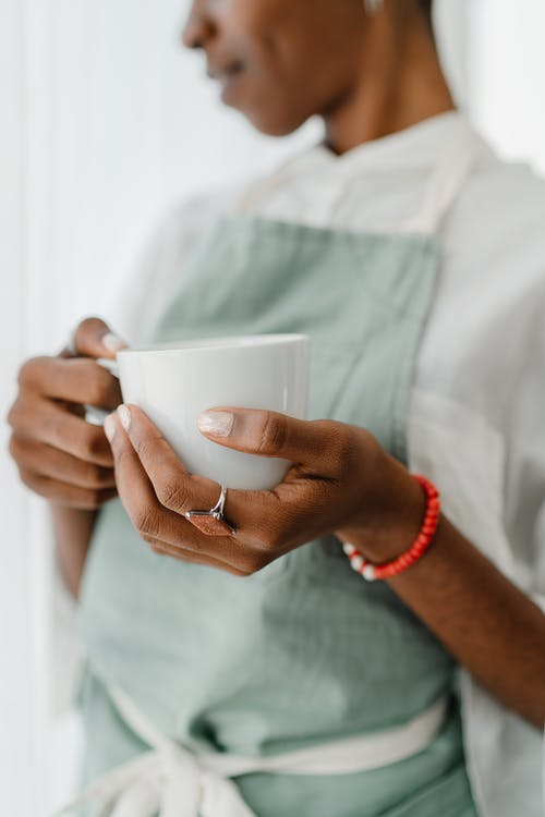 Crop black female barista with coffee mug in coffee shop