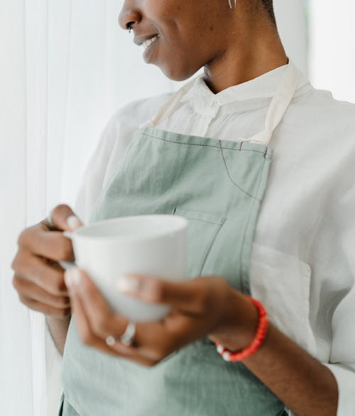 Smiling black female barista in apron standing with ceramic cup of coffee in hands during worktime in coffee house